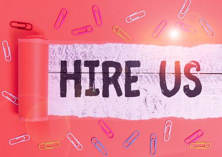 Text sign showing Hire Us. Business photo text Used by huanalysis resources indicate employee that he is got job Paper clip and torn cardboard placed above a wooden classic table backdrop 写真素材