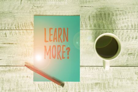 Writing note showing Learn More question. Business concept for gain knowledge or skill studying practicing Stationary placed next to a cup of black coffee above the wooden table