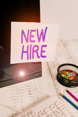 Conceptual hand writing showing New Hire. Concept meaning someone who has not previously been employed by the organization Note paper taped to black screen near keyboard stationary