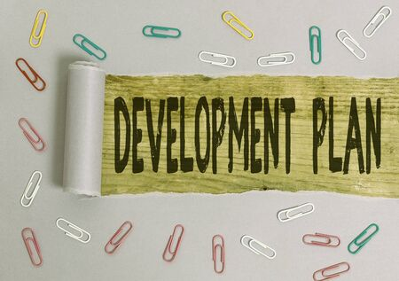 Conceptual hand writing showing Development Plan. Concept meaning the planning of the development of an area of land Paper clip and torn cardboard on wood classic table backdrop
