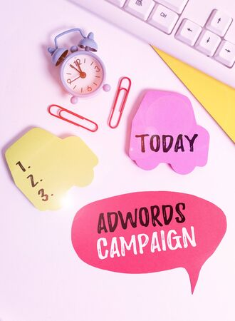 Writing note showing Adwords Campaign. Business concept for strategy for targeting right visitors with right keywords Flat lay with copy space on bubble paper clock and paper clips