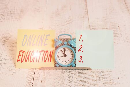 Conceptual hand writing showing Online Education. Concept meaning kind of learning that takes place via the Internet Mini blue clock standing above buffer wire between two paper