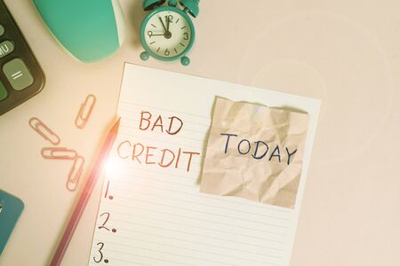 Text sign showing Bad Credit. Business photo showcasing inability of a demonstrating or company to repay a debt on time Calculator clips clock clipboard mouse sheet note pencil color background Stock fotó