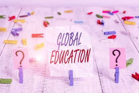 Handwriting text Global Education. Conceptual photo ideas taught to enhance one s is perception of the world Scribbled and crumbling sheet with paper clips placed on the wooden table