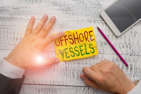 Handwriting text Offshore Vessels. Conceptual photo ship designed to supply offshore oil and gas platforms Hand hold note paper near writing equipment and modern smartphone device
