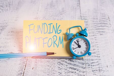 Handwriting text Funding Platform. Conceptual photo service that allows investments to be bought online Mini blue alarm clock stand tilted above buffer wire in front of notepaper