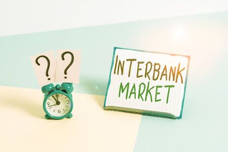 Conceptual hand writing showing Interbank Market. Concept meaning forex market where banks exchange different currencies Alarm clock beside a Paper sheet placed on pastel backdrop Stock Photo