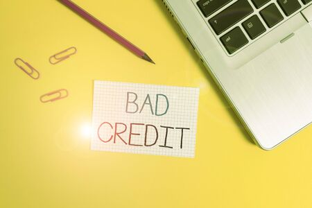 Word writing text Bad Credit. Business photo showcasing inability of a demonstrating or company to repay a debt on time Trendy metallic laptop clips pencil squared paper sheet colored background