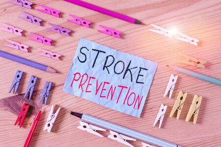 Conceptual hand writing showing Stroke Prevention. Concept meaning identified demonstratingal risk factors and change lifestyle Colored crumpled papers wooden floor background clothespin 스톡 콘텐츠