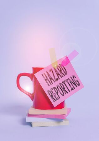 Writing note showing Hazard Reporting. Business concept for account or statement describing the danger or risk Cup colored sticky note banners stacked pads lying pastel background