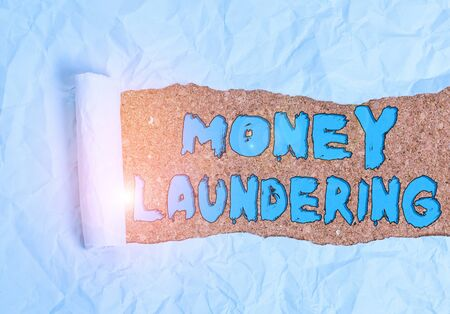 Word writing text Money Laundering. Business photo showcasing concealment of the origins of illegally obtained money Cardboard which is torn in the middle placed above a wooden classic table