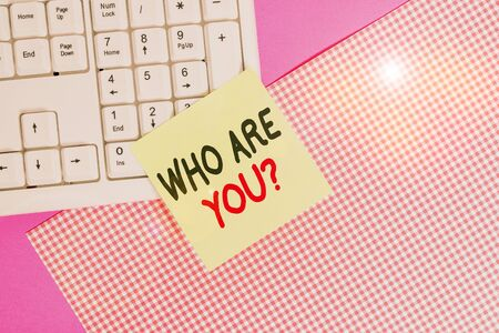 Text sign showing Who Are You question. Business photo text asking about demonstrating identity or information Note paper stick to computer keyboard near colored gift wrap sheet on table