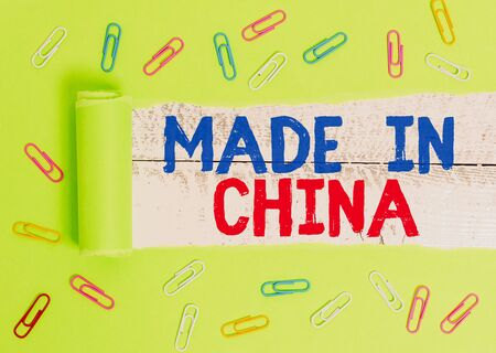 Text sign showing Made In China. Business photo text Wholesale Industry Marketplace Global Trade Asian Commerce Paper clip and torn cardboard placed above a wooden classic table backdrop Stock fotó