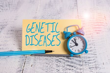 Handwriting text Genetic Diseases. Conceptual photo disease caused by an abnormality in an individual s is genome Mini blue alarm clock stand tilted above buffer wire in front of notepaper