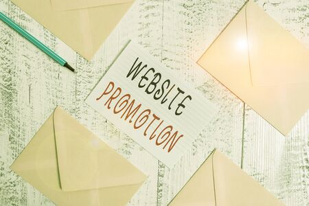 Conceptual hand writing showing Website Promotion. Concept meaning increase exposure of a website to bring more visitors Envelopes highlighter ruled paper sheet wooden vintage background