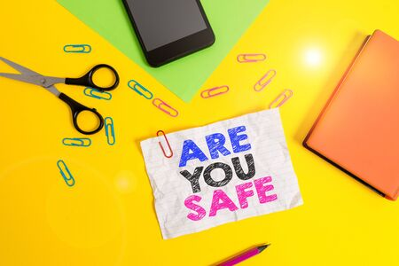Text sign showing Are You Safe. Business photo text Free from danger Not anticipating any Harm Hurt physically Paper sheets pencil clips smartphone scissors notebook colored background Stock Photo