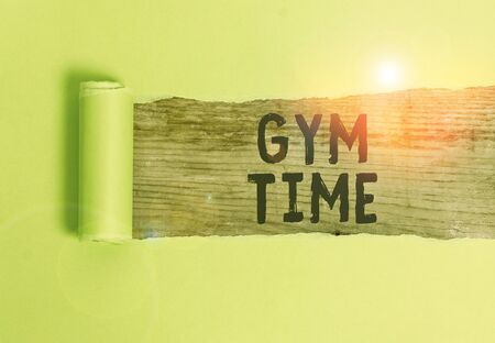 Word writing text Gym Time. Business photo showcasing a motivation to start working out making exercises fitness Cardboard which is torn in the middle placed above a wooden classic table