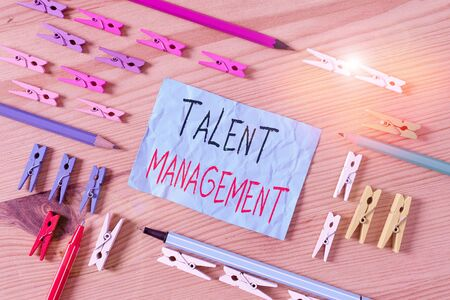 Conceptual hand writing showing Talent Management. Concept meaning anticipation of required huanalysis capital for an organization Colored crumpled papers wooden floor background clothespin