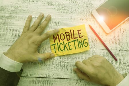 Handwriting text Mobile Ticketing. Conceptual photo tickets arrive as a text message with a special barcode Hand hold note paper near writing equipment and modern smartphone device