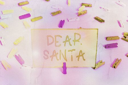 Word writing text Dear Santa. Business photo showcasing letter intended for Santa Claus written by kids during Christmas Colored clothespin papers empty reminder blue floor background office pin Stock Photo