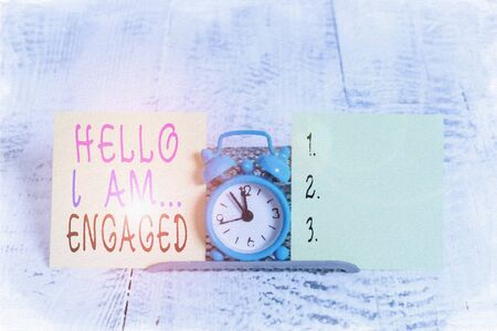 Writing note showing Hello I Am Engaged. Business concept for He gave the ring We are going to get married Wedding Mini blue alarm clock standing above buffer wire between two paper Foto de archivo