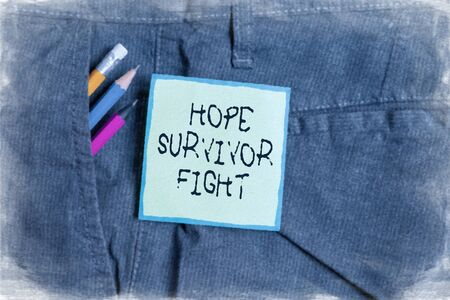 Text sign showing Hope Survivor Fight. Business photo showcasing stand against your illness be fighter stick to dreams Writing equipment and green note paper inside pocket of man work trousers