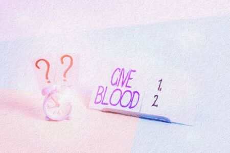 Writing note showing Give Blood. Business concept for demonstrating voluntarily has blood drawn and used for transfusions Alarm clock beside a Paper sheet placed on pastel backdrop