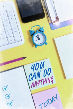 Writing note showing You Can Do Anything. Business concept for Motivation for doing something Believe in yourself White paper with copy space with paper clips clock and pc keyboard
