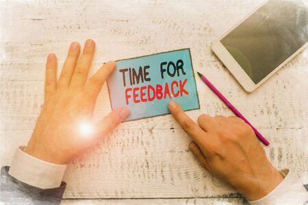 Writing note showing Time For Feedback. Business concept for Need to response or give critic on something Evaluation Hand hold note paper near writing equipment and smartphone 版權商用圖片