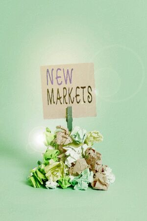 Text sign showing New Markets. Business photo showcasing market where the end product or service is new or not exist yet Reminder pile colored crumpled paper clothespin reminder blue background 写真素材