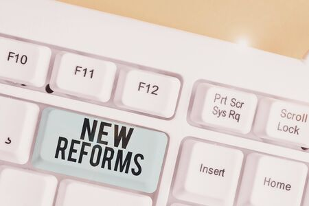 Conceptual hand writing showing New Reforms. Concept meaning to amend or improve by change of form or removal of faults White pc keyboard with note paper above the white background