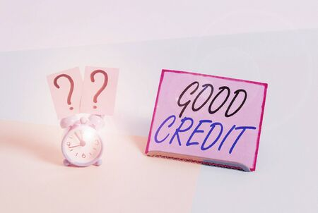Word writing text Good Credit. Business photo showcasing borrower has a relatively high credit score and safe credit risk Mini size alarm clock beside a Paper sheet placed tilted on pastel backdrop 版權商用圖片