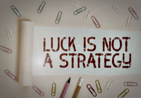 Writing note showing Luck Is Not A Strategy. Business concept for it is not being Lucky when planned intentionally Stationary and torn cardboard placed above plain pastel table backdrop Stock fotó