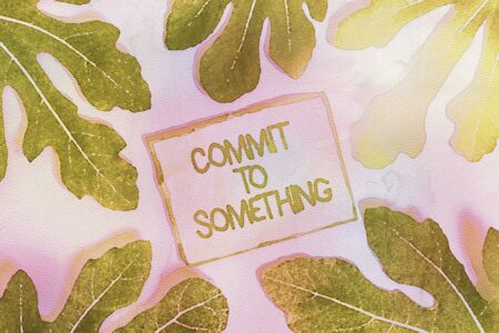 Writing note showing Commit To Something. Business concept for To Live a Life of Purpose with Pride Honor a Promise Leaves surrounding notepaper above empty soft pastel table