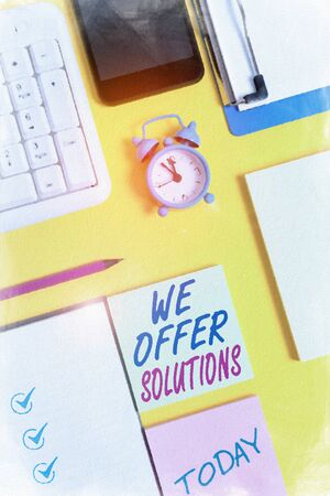 Writing note showing We Offer Solutions. Business concept for Offering help assistance Experts advice strategies ideas White paper with copy space with paper clips clock and pc keyboard