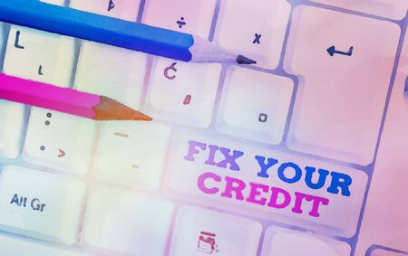 Writing note showing Fix Your Credit. Business concept for Keep balances low on credit cards and other credit White pc keyboard with note paper above the white background Stockfoto