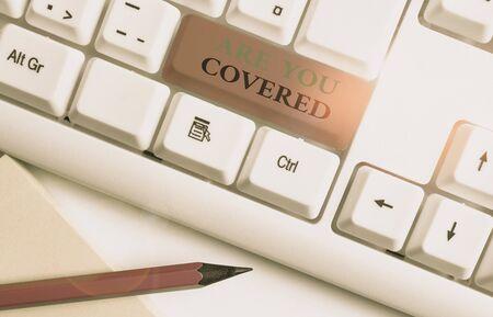 Schreiben Sie eine Notiz, die zeigt, dass Sie abgedeckt sind. Geschäftskonzept für die Frage, wie Medikamente von Ihrem Plan abgedeckt werden Weiße PC-Tastatur mit Notizpapier über dem weißen Hintergrund Standard-Bild
