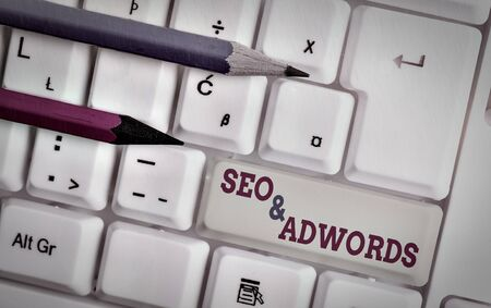 Writing note showing Seo And Ad words. Business concept for Pay per click Digital marketing Ad sense White pc keyboard with note paper above the white background