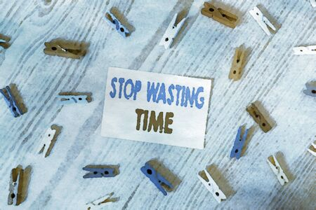 Handwriting text writing Stop Wasting Time. Conceptual photo advising demonstrating or group start planning and use it wisely Colored clothespin papers empty reminder wooden floor background office