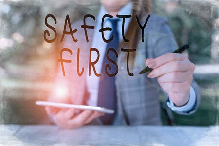 Writing note showing Safety First. Business concept for used to say that the most important thing is to be safe Female business person sitting by table holding mobile phone