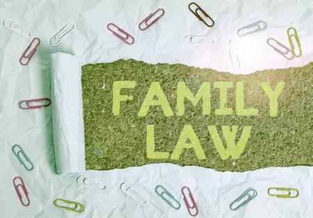 Signo de texto que muestra el derecho de familia. Texto fotográfico de negocios la rama del derecho que se ocupa de asuntos relacionados con la familia Clip de papel y cartón rasgado colocado sobre un fondo de mesa clásico de madera