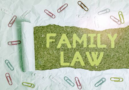 Text sign showing Family Law. Business photo text the branch of law that deals with matters relating to the family Paper clip and torn cardboard placed above a wooden classic table backdrop