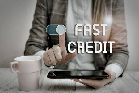 Text sign showing Fast Credit. Business photo text Apply for a fast demonstratingal loan that lets you skip the hassles Business woman sitting with mobile phone and cup of coffee on the table