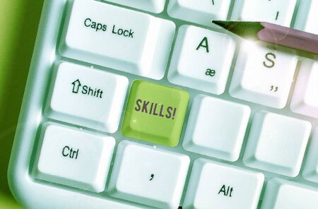 Conceptual hand writing showing Skills. Concept meaning ability do something very well by nature White pc keyboard with note paper above the white background Stock Photo - 135313768