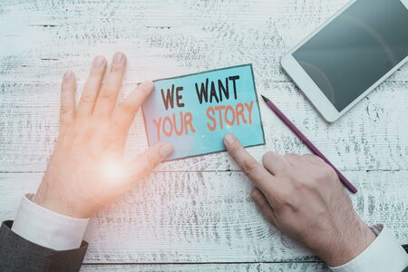 Writing note showing We Want Your Story. Business concept for Tell Us something a Glimpse About Your Life History Hand hold note paper near writing equipment and smartphone
