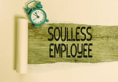 Text sign showing Soulless Employee. Business photo showcasing lack huanalysis qualities and the ability to produce feelings Alarm clock and torn cardboard placed above a wooden classic table backdrop