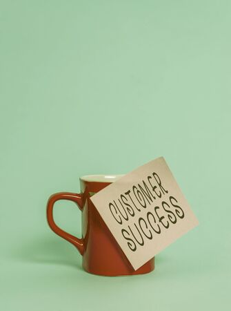 Text sign showing Customer Success. Business photo showcasing customers achieve desired outcomes while using your product Coffee tea cup mug colored sticky note lying beautiful pastel background Archivio Fotografico