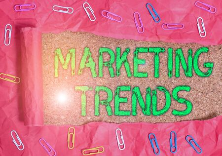 Conceptual hand writing showing Marketing Trends. Concept meaning changes and developments in trading in the market Paper clip and torn cardboard on wood classic table backdrop