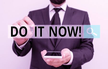 Text sign showing Do It Now. Business photo showcasing not hesitate and start working or doing stuff right away Male human wear formal work suit hold smart hi tech smartphone use one hand 版權商用圖片