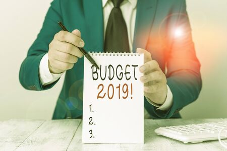 Text sign showing Budget 2019. Business photo showcasing estimate of income and expenditure for current year Man holds empty paper with copy space in front of him Copy Space